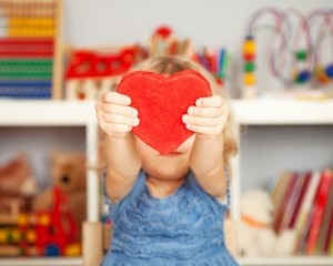 Toddler girl handing a large toy heart