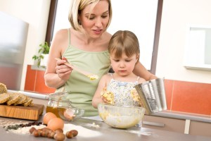 Mother and toddler daughter making working in kitchen together